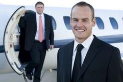 Junge Geschäftsmänner vor Geschäftsflugzeug Stockbilder
