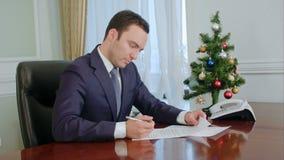 Junge Geschäftsmannlesedokumente und Unterzeichnen es durch den Schreibtisch nahe neues Jahr-Baum stock video footage