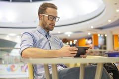 Junge Geschäftsmannsitzplätze auf Tabelle in restoran und des Gebrauches beweglichem De Stockfoto