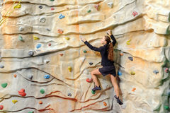 Junge Geschäftsfrau auf Felsenwand Stockfotos