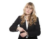 Junge Geschäftsfrau, die auf ihre Uhr zeigt Stockbild