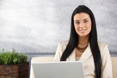 Junge Geschäftsfrau, die an dem Laptoplächeln arbeitet Stockfotos