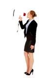 Junge Geschäftsfrau, die durch Megaphon schreit Stockbild