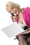 Junge Geschäftsfrau, die eine Laptop-Computer und einen Mobilhandy verwendet Stockfotos