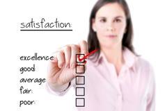 Junge Geschäftsfrau, die hervorragende Leistung auf Kundenzufriedenheitsumfrageform überprüft. Lizenzfreies Stockfoto