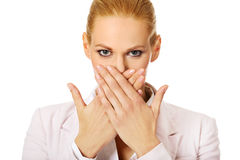 Junge Geschäftsfrau, die ihren Mund mit zwei Händen bedeckt Stockfotos