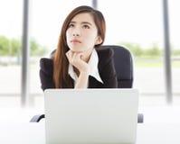 Junge Geschäftsfrau, die im Büro denkt Lizenzfreies Stockbild