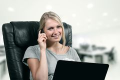 Junge Geschäftsfrau, die Laptop und Telefon im Büro verwendet Stockfoto