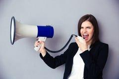 Junge Geschäftsfrau, die mit Megaphon schreit Lizenzfreies Stockfoto