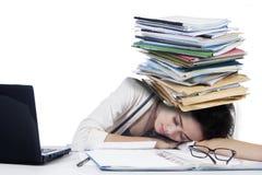 Junge Geschäftsfrau, die mit Schreibarbeit schläft Stockfoto