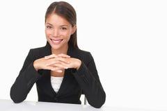 Junge Geschäftsfrau, die am Schreibtisch sitzt Lizenzfreie Stockfotos