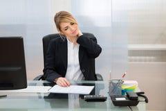 Junge Geschäftsfrau, die unter neckache leidet Lizenzfreies Stockbild