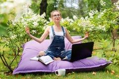 Junge Geschäftsfrau, die Yoga außerhalb des Bürogebäudes sitzt in Lotussitz im Park mit ihrem Laptop und Tasse Tee oder Co tut Lizenzfreie Stockbilder