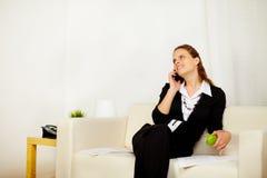 Junge Geschäftsfrau, die zu Hause an Sofa arbeitet Lizenzfreie Stockfotografie