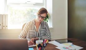 Junge Geschäftsfrau Writing Notes auf ihrem Schreibtisch Stockfotos