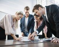 Junge Geschäftsleute, die am Konferenztische gedanklich lösen Stockbilder