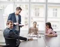Junge Geschäftsleute, die Laptop in der Sitzung betrachten Lizenzfreie Stockfotos