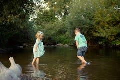 Junge Geschwister, die im Fluss spielen Lizenzfreie Stockfotografie