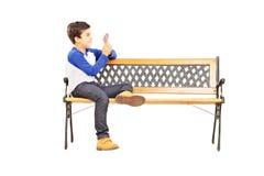 Junge gesetzt auf Bank und Spielkarten mit imaginärem Freund lizenzfreie stockfotografie