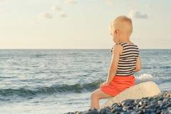 Junge in gestreifter Weste sitzt auf einem Felsen durch das Meer Rückseitige Ansicht Stockbild