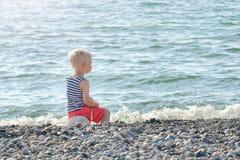 Junge in gestreifter Weste sitzt auf einem Felsen durch das Meer Rückseitige Ansicht Stockfotografie