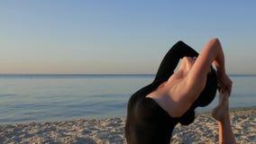 Junge gesunde Eignungsfrau im schwarzen Bodysuit, der Yoga durch das Meer bei Sonnenaufgang tut Konzept, Genuss, Harmonie 4K Vide stock video