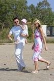Junge, gesunde Familie, die entlang einen sonnigen Strand geht Stockfoto