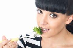 Junge gesunde Frau, die einen gesunden frischen grünen Blätter getriebenen Salat mit Tomate isst Stockfotos