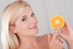 Junge gesunde Frau mit einer Orange Lizenzfreie Stockbilder