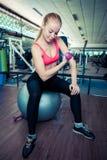 Junge gesunde Frau tun körperliche Bewegungen mit Dummköpfen auf Sitzball in der Turnhalle Lizenzfreies Stockbild