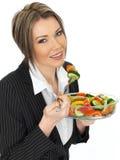 Junge gesunde Geschäftsfrau, die einen frischen Mischsalat isst Stockfotos
