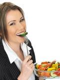 Junge gesunde Geschäftsfrau, die einen frischen Mischsalat isst Stockfotografie