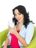 Junge gesunde glückliche Frau, die ein frisches Glas Milch hält Lizenzfreie Stockbilder