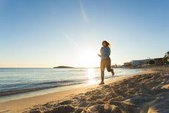 Junge gesunde Lebensstileignungsfrau, die am Sonnenaufgangstrand läuft Lizenzfreies Stockbild