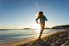 Junge gesunde Lebensstileignungsfrau, die am Sonnenaufgangstrand läuft Stockfotografie