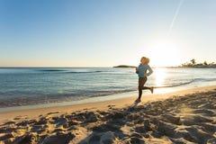 Junge gesunde Lebensstileignungsfrau, die am Sonnenaufgangstrand läuft Lizenzfreie Stockbilder