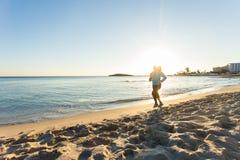 Junge gesunde Lebensstileignungsfrau, die am Sonnenaufgangstrand läuft Stockfoto