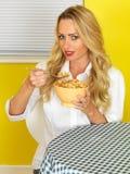 Junge gesunde schauende Frau, die Frühstückskost aus Getreide isst lizenzfreie stockfotos