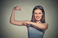 Junge gesunde vorbildliche Frau des schönen Sitzes, welche die Muskeln zeigen ihr Stärke biegt Stockbild