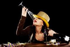 Junge getrunkene Frau, die durch einen Schreibtisch sitzt. Lizenzfreie Stockfotografie