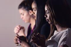 Junge gewidmete Frauen, die zusammen beten Stockbild