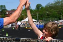 Junge gewinnt das Rennen, beglückwünscht vom Trainer Lizenzfreie Stockfotos