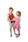 Junge gibt Apfel des kleinen Mädchens Lizenzfreies Stockbild
