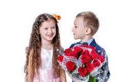 Junge gibt einem Mädchen Blumen am Tag St. valentine Lizenzfreie Stockfotografie