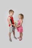 Junge gibt Mädchenblumenstrauß von Gänseblümchen auf Grau lizenzfreies stockbild
