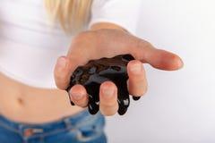 Junge girl's Hand, die schwarzen Schlamm hält Stockfoto