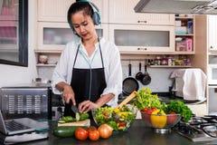 Junge Glück Frau, die Gemüsesalat in der Küche, H kocht Lizenzfreie Stockbilder