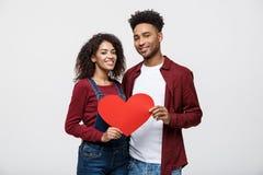 Junge glückliche Afroamerikanerpaare in der Liebe, die rotes Papierherz hält Lizenzfreies Stockbild
