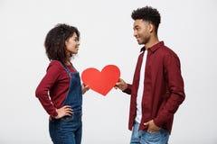 Junge glückliche Afroamerikanerpaare in der Liebe, die rotes Papierherz hält Stockfotos