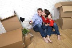 Junge glückliche amerikanische Paare, die auf dem Boden macht selfie Foto feiert das Bewegen in neues Haus oder in Wohnung sitzen Lizenzfreie Stockbilder